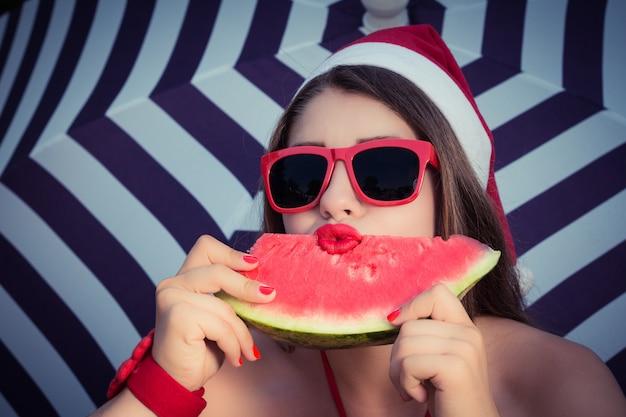 Portret śmieszna dziewczyna w święty mikołaj kapeluszu i czerwonych okularach przeciwsłonecznych z plasterkiem arbuza