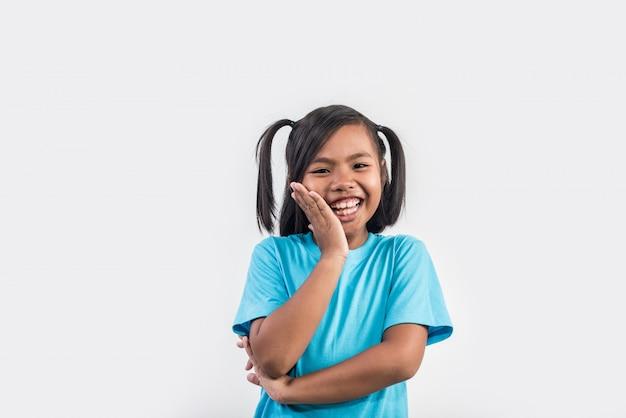 Portret śmieszna mała dziewczynka postępuje w studio strzale