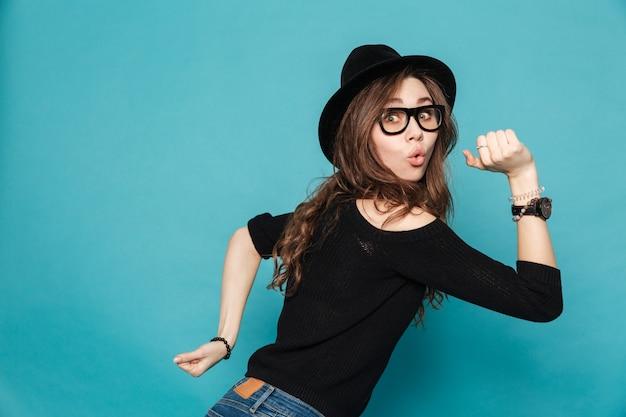 Portret śmieszna młoda śliczna dziewczyna w kapeluszowym bieg