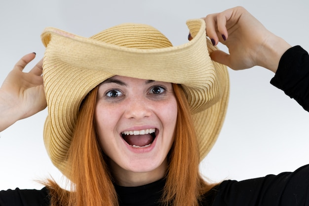 Portret śmieszna rudzielec kobieta w torba żółtym słomianym kapeluszu.