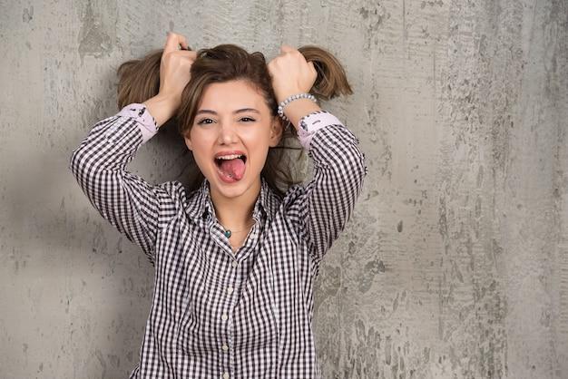 Portret śmieszne dziewczyna robi dwa kucyki na głowie rękami.