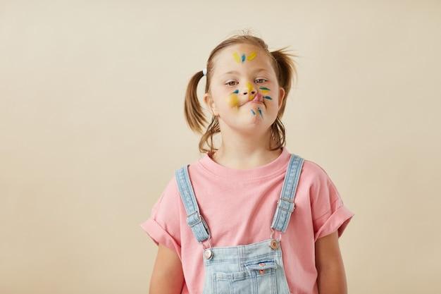 Portret śmieszne dziewczynki z pomalowaną twarzą pozowanie na kamery na białym tle