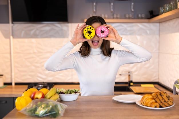 Portret śmieszne młoda biała kobieta zakrywając oczy pączkami w nowoczesnej kuchni. koncepcja fast foodów.