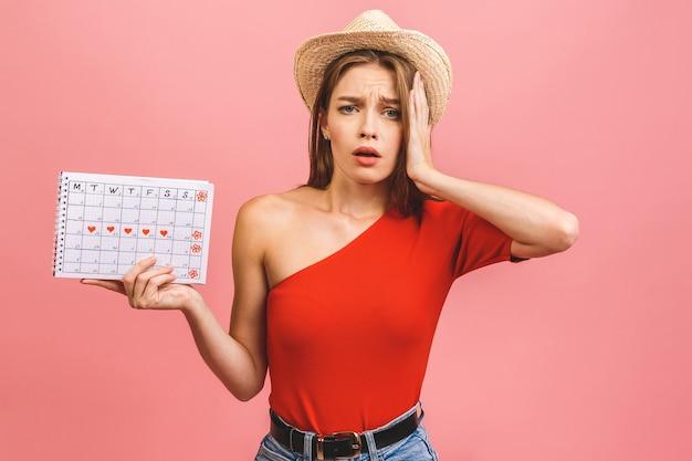 Portret śmieszne młoda dziewczyna trzyma kalendarz okresów na białym tle na różowym tle