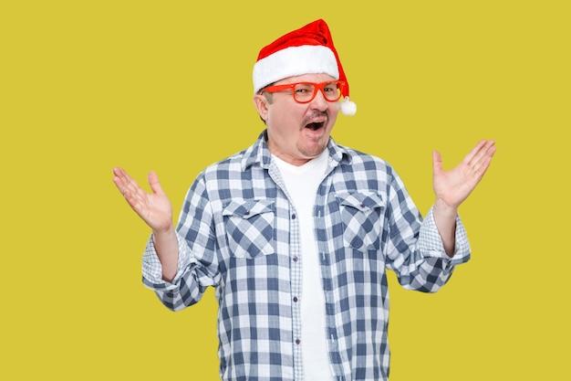 Portret śmieszne nowoczesne mężczyzna w średnim wieku w czerwonym kapturku, okulary i kraciaste koszule stojący z rękami w górze i zaskoczony twarz patrząc na kamery. wewnątrz, studio strzał, na białym tle na żółtym tle