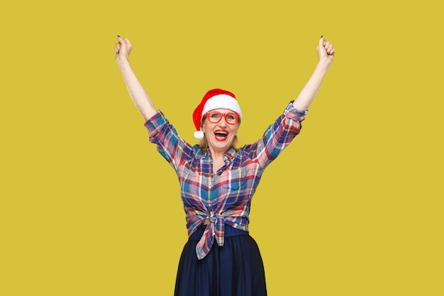 Portret śmieszne nowoczesnej kobiety w wieku w czerwonej czapce santa i okulary kraciaste koszule stojący z rękami do góry iz zaskoczoną miną patrząc na kamery. wewnątrz, strzał studyjny, żółte tło