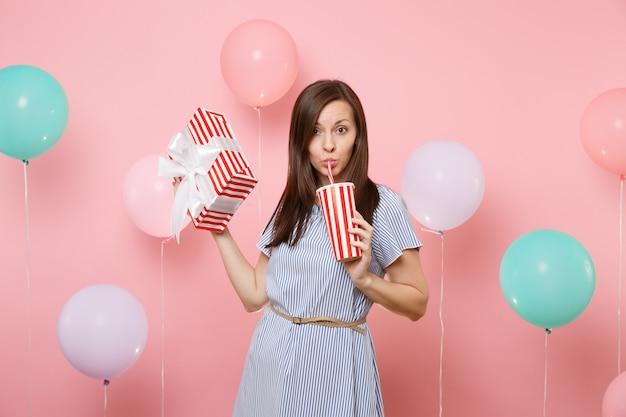 Portret śmieszne piękne kobiety w niebieskiej sukience trzymającej czerwone pudełko z prezentem przedstawia sodę lub colę z plastikowego kubka na pastelowym różowym tle z kolorowymi balonami. urodzinowe przyjęcie świąteczne.
