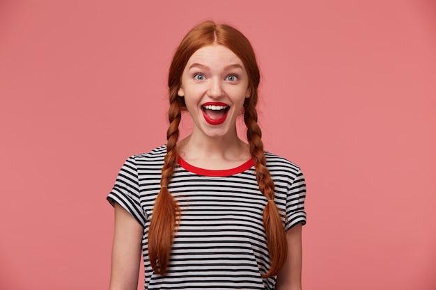 Portret śmieszne rudowłosa europejska kobieta z plecioną fryzurą, uśmiechając się szeroko, wyrażając emocje na białym tle. młoda mama patrzy na swojego uroczego syna bawiącego się z psem