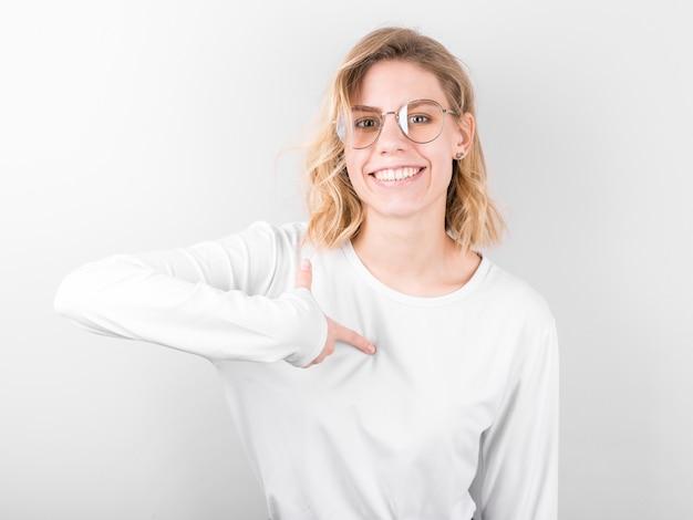 Portret śmieszne uśmiechnięta kobieta, wskazując palcami na siebie na białym tle