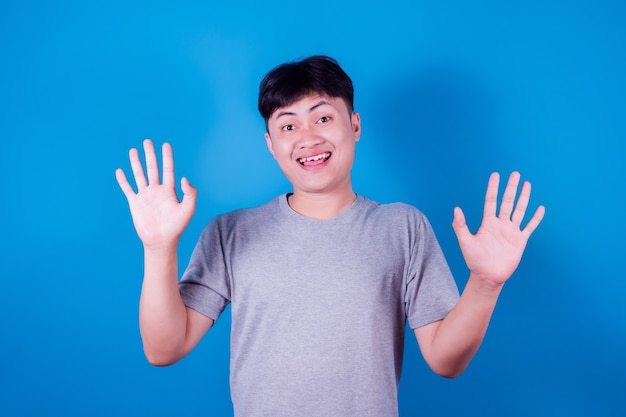 Portret śmiesznego azjatyckiego mężczyzny w szarej koszulce uśmiechającego się na niebieskim tle