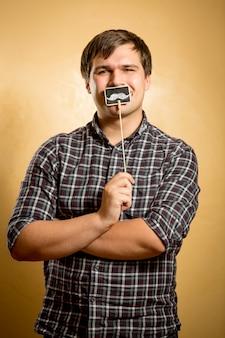 Portret śmiesznego mężczyzny trzymającego fałszywe wąsy na patyku przy ustach