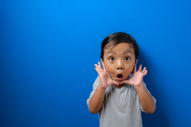 Portret śmiesznego młodego azjatyckiego chłopca patrzącego na kamerę z dużymi oczami zakrywającymi usta, zszokowany zdziwiony wyraz twarzy na niebieskim tle