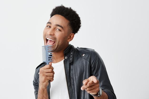 Portret śmiesznego młodego czarnoskórego mężczyzny z ciemnymi kręconymi włosami w swobodnej białej koszulce i skórzanej kurtce trzymającej grzebień w rękach, udając, że śpiewa z mikrofonem, przygotowując się do spotkania.