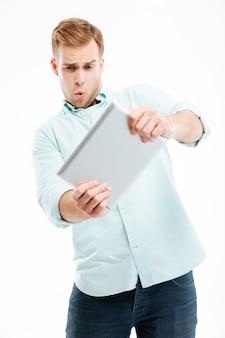 Portret śmiesznego rudego mężczyzny korzystającego z komputera typu tablet na białym tle na białej ścianie