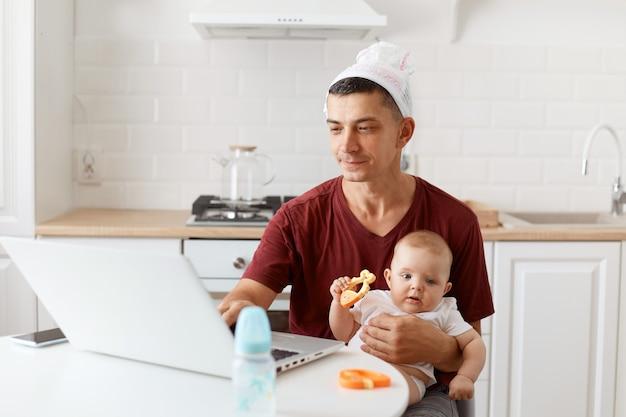 Portret śmiesznego skoncentrowanego, przystojnego freelancera, ubrany w bordową koszulkę, pozowanie w białej kuchni, siedzący przed laptopem z dzieckiem w rękach i pracujący.