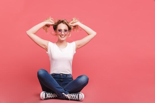 Portret śmiesznej blond kobiety noszącej okulary przeciwsłoneczne w stylu vintage, śmiejąc się siedząc na podłodze z nogami skrzyżowanymi na białym tle nad różową ścianą