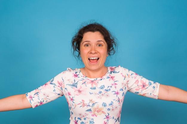 Portret śmiesznej emocjonalnej młodej kobiety na niebieskim tle