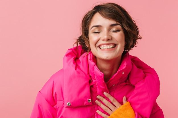 Portret śmiesznej kaukaskiej kobiety w ciepłym płaszczu śmiejącej się na różowo