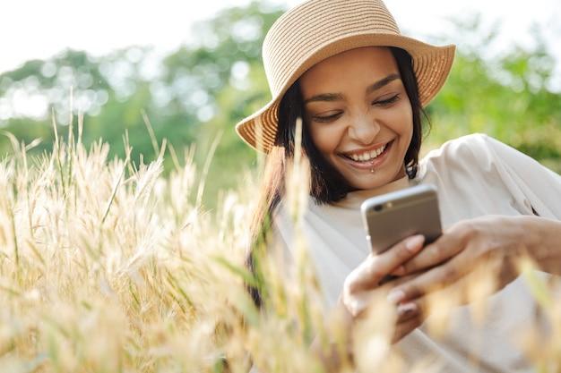 Portret śmiesznej kobiety noszącej przekłuwanie warg i słomkowy kapelusz, pisząc na telefonie komórkowym, leżąc na trawie w zielonym parku