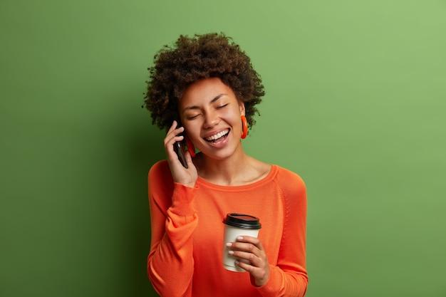 Portret śmiesznej kobiety z kręconymi włosami, radośnie się śmieje, rozmawia przez telefon, bawi się przyjacielem, pije kawę z jednorazowego kubka, ubrana niedbale, zamyka oczy
