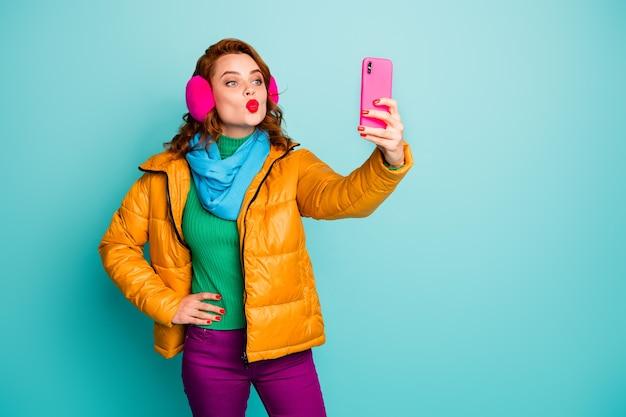 Portret śmiesznej ładnej damy trzymającej telefon za ręce robiąc selfie, wysyłając pocałunki w powietrzu nosić na co dzień nauszniki żółty płaszcz szalik magenta spodnie sweter.