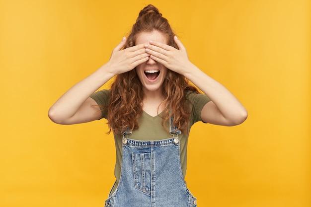 Portret śmiesznej młodej rudej suczki ma na sobie niebieski kombinezon i zieloną koszulkę, uśmiecha się szeroko i zamyka oczy dłońmi, czekając na niespodziankę. na białym tle nad żółtą ścianą