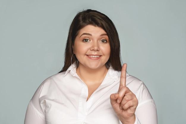 Portret śmiesznej, ślicznej plus size młodej kobiety w białej koszuli pokazującej palec wskazujący, jakby próbującej zwrócić na siebie uwagę, uśmiechającej się szeroko. ludzkie emocje, uczucia i reakcje