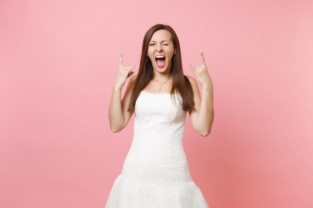 Portret śmiesznej szalonej kobiety w białej sukni, stojącej, mrugającej i pokazującej znak rock-n-roll
