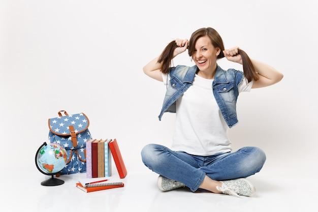 Portret śmiesznej szalonej roześmianej studentki w dżinsowych ubraniach, trzymającej kucyki, siedzącej w pobliżu kuli ziemskiej, plecaka, podręczników szkolnych na białym tle