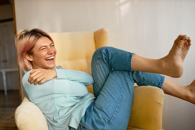 Portret śmiesznej uroczej młodej kobiety boso z różowawymi włosami i kolczykiem na twarzy, śmiejąc się głośno, dobrze się bawiąc w domu, siedząc wygodnie w fotelu.