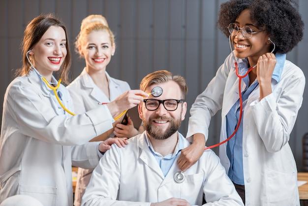 Portret śmiesznej wieloetnicznej grupy naukowców lub studentów medycyny siedzących razem w biurze lub w klasie