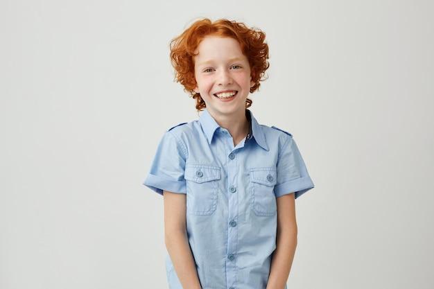 Portret śmieszny chłopiec z czerwonym włosy i piegów ono uśmiecha się