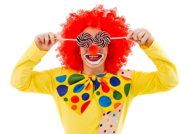 Portret śmieszny figlarnie błazen w czerwonej peruce zakrywa jego oczy