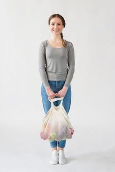 Portret smiley młoda kobieta trzyma torbę wielokrotnego użytku