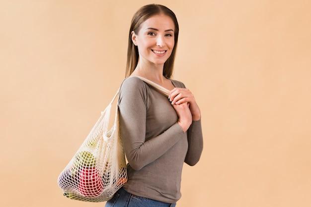 Portret smiley młodej kobiety przewożenia torba z sklepami spożywczymi