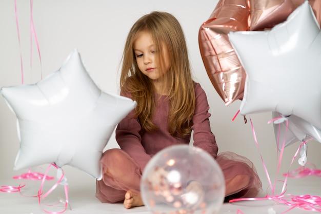 Portret smutna blond mała dziewczynka z kolorowymi balonami
