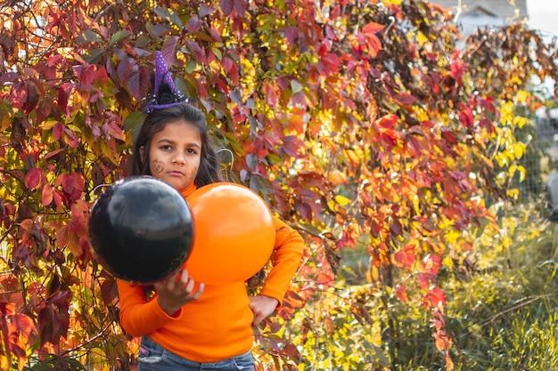 Portret smutna dziewczyna z brązowymi włosami bieganie i skakanie. śmieszne dzieci w strojach karnawałowych na świeżym powietrzu.