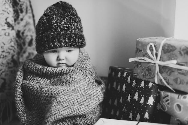 Portret smutna dziewczynka w pokoju siedzi na prezenty.