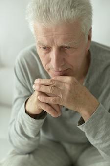 Portret smutnego starszego mężczyzny w domu