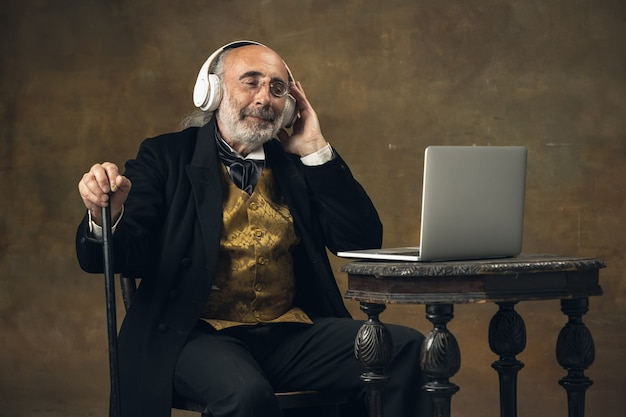 Portret smutnego starszego szarowłosego dżentelmena arystokraty lub aktora izolowanego na ciemnej ścianie