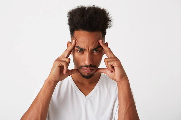 Portret smutnego, zdenerwowanego młodego człowieka z kręconymi włosami nosi koszulkę, wygląda na przygnębionego i zakrzywione usta na białym tle na białej ścianie