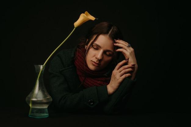 Portret smutnej dziewczyny w płaszczu i szaliku z kwiatem w stylu vintage