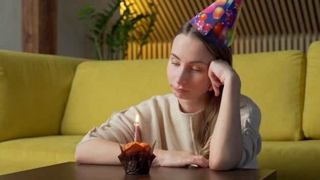 Portret smutnej dziewczyny z kawałkiem ciasta ze świecą, dziewczyna zdmuchuje świecę