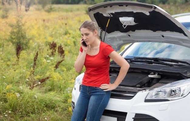 Portret smutnej kobiety opierającej się na zepsutym samochodzie z otwartą maską i rozmawiającej przez telefon