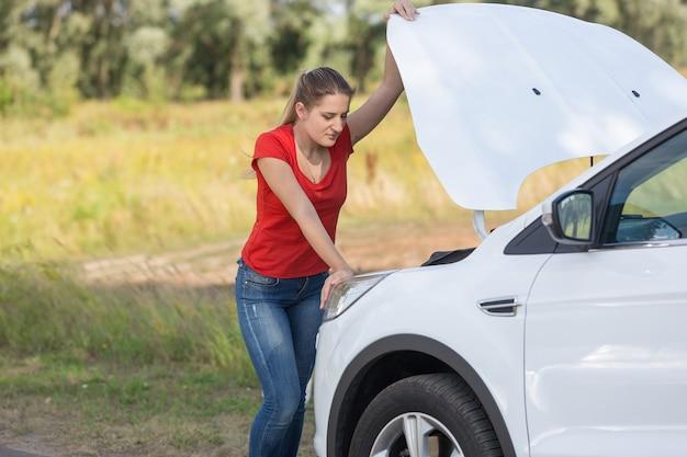 Portret smutnej kobiety stojącej przy zepsutym samochodzie z otwartym kapturem
