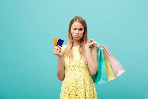 Portret smutnej kobiety trzymającej torby na zakupy i kartę bankową na białym tle na niebieskim tle