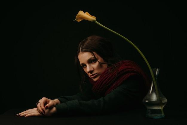 Portret smutnej kobiety w płaszczu i szaliku z kwiatem w stylu vintage