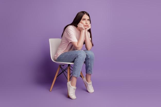 Portret smutnej nieszczęśliwej kobiety siedzi na krześle myślę na białym tle na fioletowym tle