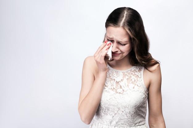Portret smutnej, nieszczęśliwej płaczącej kobiety z piegami i białą sukienką i eleganckim zegarkiem na srebrnoszarym tle. miejsce na kopię. koncepcja opieki zdrowotnej i medycyny.