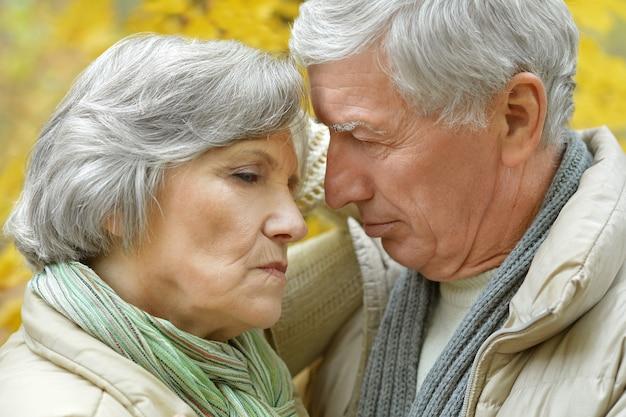 Portret smutnej pary starszych w jesiennym parku